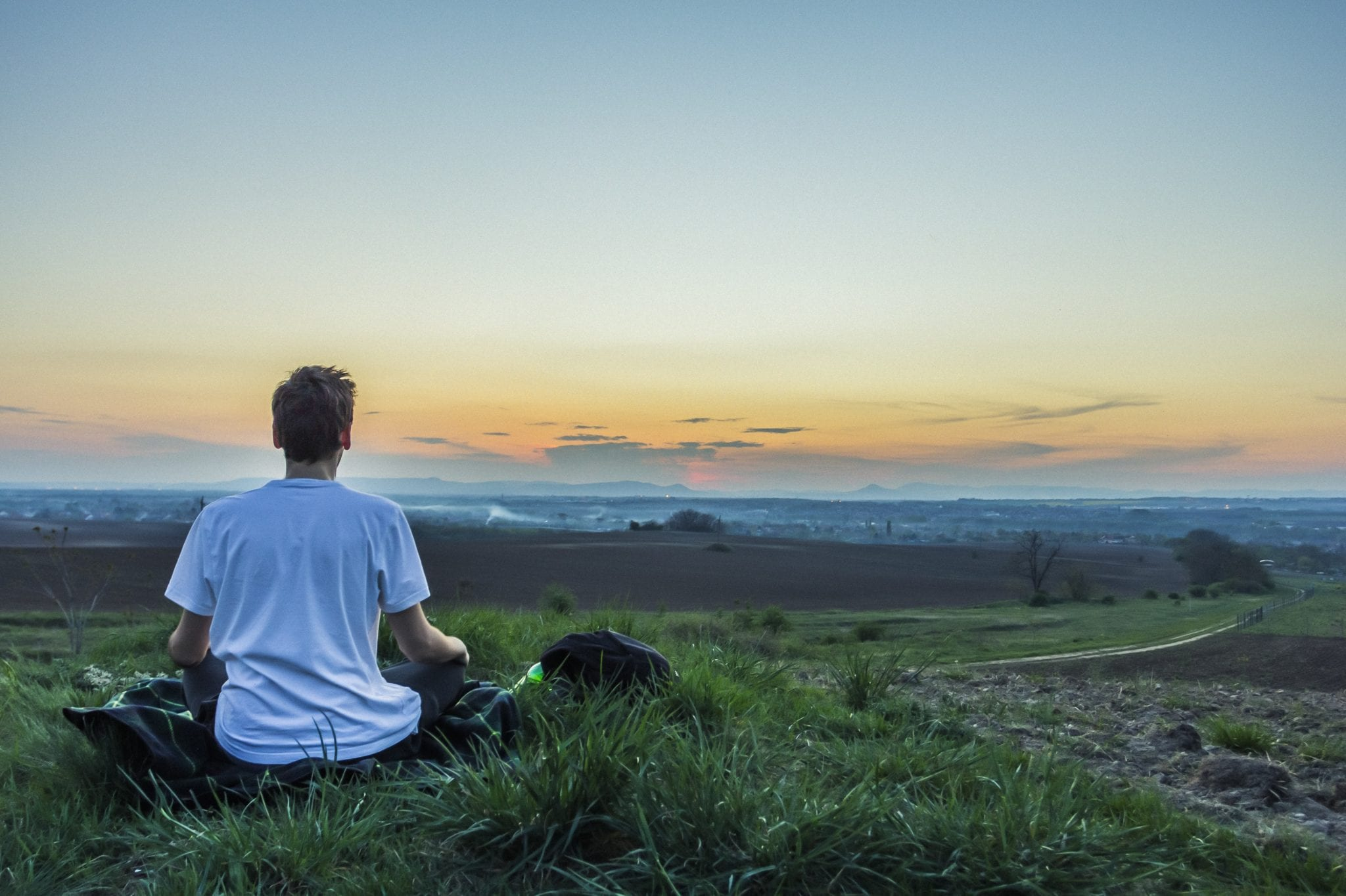 Man sitting and meditating towards the mountains